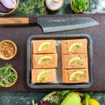 Salmon Medallions by Xara Catering with lemon wedges on a wooden board with herbs and vegetables